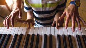 Дети и руки женщин на ключах рояля стоковая фотография