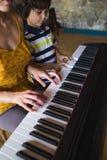 Дети и руки женщин на ключах рояля стоковое изображение rf