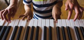 Дети и руки женщин на ключах рояля стоковые фото