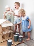 Дети как взрослые: Мальчик и девушка покрасить кукольный дом белым и получить грязным с краской Подлинное фото стоковое изображение