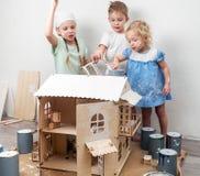 Дети как взрослые: Мальчик и девушка покрасить кукольный дом белым и получить грязным с краской Подлинное фото стоковое изображение rf