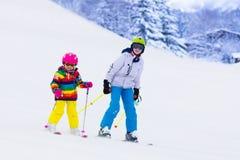 Дети катаясь на лыжах в горах Стоковое фото RF