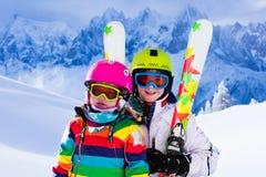 Дети катаясь на лыжах в горах Стоковое Фото