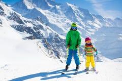 Дети катаясь на лыжах в горах Стоковые Фотографии RF