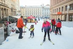 Дети катаясь на лыжах на наклоне лыжи Стоковые Изображения