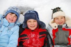 Дети кладя в снежок Стоковые Изображения RF