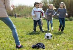 Дети, который побежали к футбольному мячу лежа на траве Стоковое фото RF