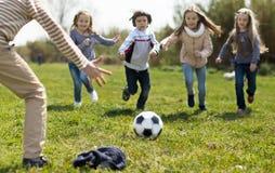 Дети, который побежали к футбольному мячу лежа на траве Стоковые Изображения