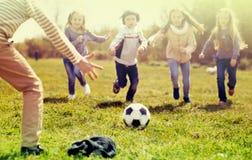 Дети, который побежали к футбольному мячу лежа на траве Стоковое Изображение