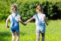 Дети, который побежали на зеленой траве держа руки стоковая фотография