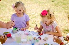 Дети крася камни outdoors стоковое фото