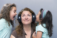 Дети кричащие на матери пока она слушая к музыке Стоковые Изображения
