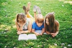Дети лежа на зеленой траве и читая книгу рассказа Стоковые Фотографии RF