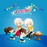 Дети льют воду на руках revered старейшин и просят благословлять с тайской каллиграфией Songkran и флагов Стоковые Фотографии RF