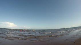 Дети людей главным образом имея потеху купая в море во время горячего лета Отслеживать съемку акции видеоматериалы