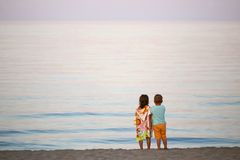 Дети мальчик и романс девушки на заходе солнца seashore красочном Стоковое Изображение