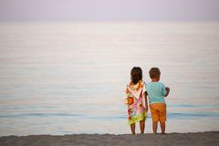 Дети мальчик и романс девушки на заходе солнца seashore красочном Стоковое фото RF