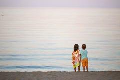 Дети мальчик и романс девушки на заходе солнца seashore красочном Стоковое Фото