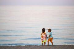 Дети мальчик и романс девушки на заходе солнца seashore красочном Стоковая Фотография RF