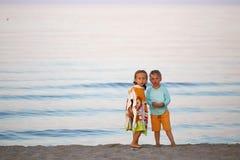 Дети мальчик и романс девушки на заходе солнца seashore красочном Стоковая Фотография