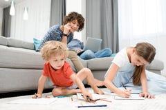 Дети матери наблюдая дома Стоковые Фотографии RF