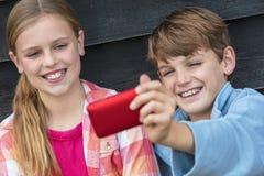 Дети мальчика и девушки принимая сотовый телефон Selfie Стоковые Изображения