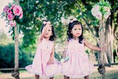 Дети 2 милых маленькой девочки сидя на качании Стоковая Фотография