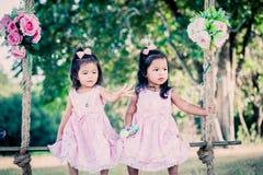 Дети 2 милых маленькой девочки сидя на качании Стоковые Фотографии RF