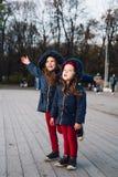 Дети моды в парке осени Близкий поднимающий вверх портрет образа жизни 2 красивых кавказских девушек outdoors, нося милое ультрам стоковое изображение rf