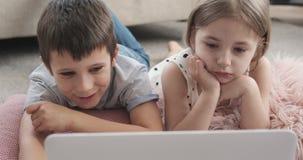 Дети наслаждаясь фильмом на ноутбуке видеоматериал