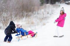 Дети наслаждаясь ездой ловкости на зимний день стоковые изображения rf