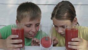 Дети на белой предпосылке выпивают сок томата от стекел Сок томата питья 2 мальчиков акции видеоматериалы