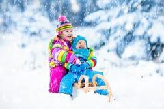 Дети на езде саней Бросаться через снег Потеха снега зимы Стоковая Фотография