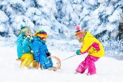 Дети на езде саней Бросаться через снег Потеха снега зимы Стоковые Изображения RF