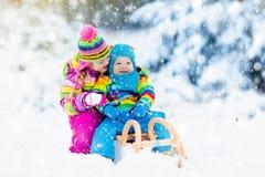 Дети на езде саней Бросаться через снег Потеха снега зимы Стоковые Фото