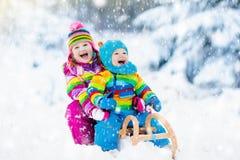 Дети на езде саней Бросаться через снег Потеха снега зимы Стоковые Изображения