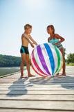Дети на озере с шариком пляжа Стоковые Изображения RF
