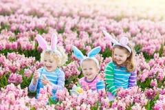Дети на пасхальном яйце охотятся в зацветая саде Стоковое Изображение RF