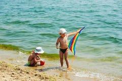 Дети на пляже играя с змеем Стоковая Фотография