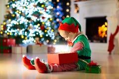 Дети на рождественской елке Дети раскрывают настоящие моменты стоковое фото rf