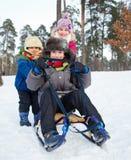 Дети на скелетонах в снеге Стоковая Фотография