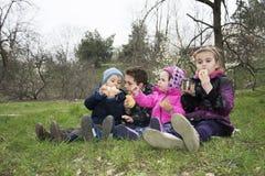 Дети на луге весны сидят на траве и едят печенья Стоковая Фотография