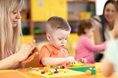 Дети на уроке в детском саде Малыш младенца играя с пластилином с учителем в игровой питомника стоковое изображение