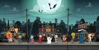 Дети нося костюмы извергов идя в фокусы городка или концепцию праздника знамени хеллоуина обслуживания счастливую стоковая фотография rf