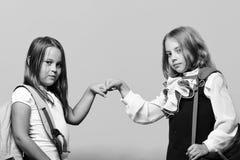 Дети нося schoolbags побили каждые другие кулаки Стоковые Фото
