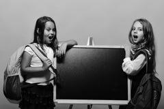 Дети нося schoolbags полагаются на сияющем классн классном, копируют космос Стоковые Фотографии RF