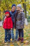 Дети обнимая среди парка осени Стоковые Фотографии RF