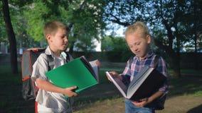 Дети образование, школьники мальчик и девушка с книгами в руках прочитанных после уроков стоя в парке сток-видео