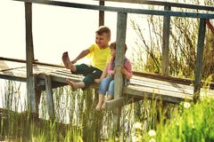 Дети ослабляют сидеть на деревянном мосте рекой Стоковое Изображение