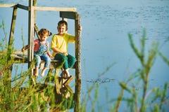 Дети ослабляют сидеть на деревянном мосте рекой Стоковые Фото